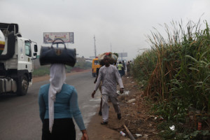 Weeds takes over pedestrian walk way as pedestrains struggle to pass in between the high way and the walk way at Pakuro bus stop in Mowe area of Ogun state.