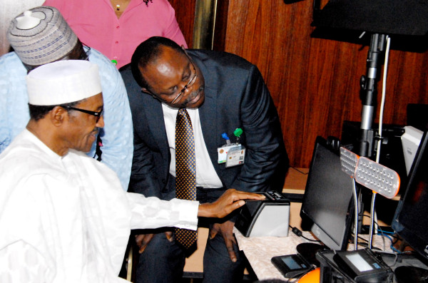 President Muhammadu Buhari being assisted  by the Director – general –CEO of National Identity Management Commission , Mr.Chris Onyemenam during Biometric Capturing of the National Identity card held at the Presidential Villa, Abuja …today. Photo: GODWIN OMOIGUI