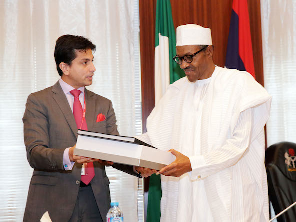 Mr Jaimal Shergill, a member of the Centenary City project presents some documents to President Buhari