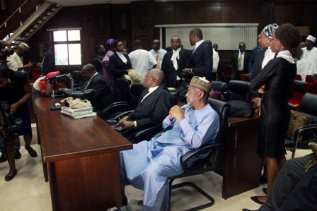 Dasuki Sambo, in blue, surrounded by lawyers in court today