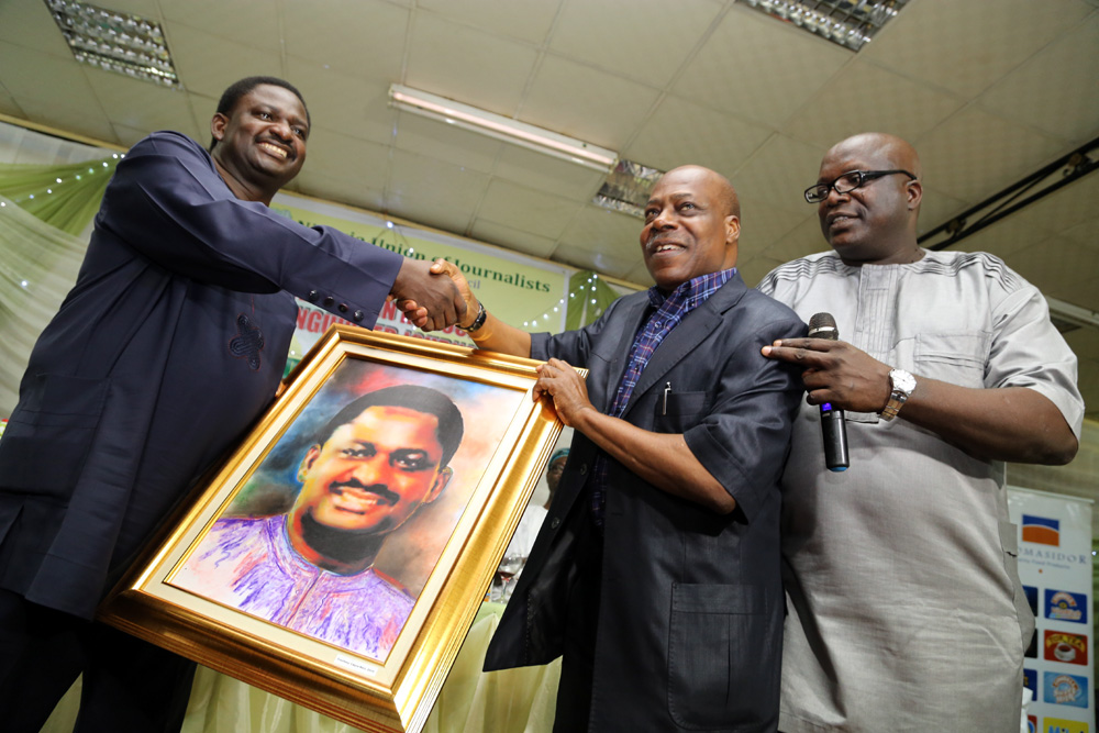 Femi Adesina, Special Adviser on Media and Publicity to President Mohammad Buhari receiving his portrait picture from Mr Ray Ekpu and Chairman, NUJ, Lagos State, Mr Deji Elumoye, during the occasion