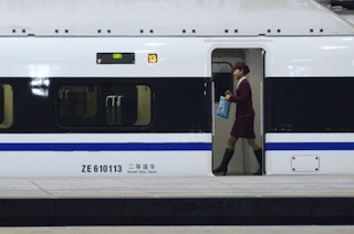 A stewardess walks inside a high-speed train running from the Beijing to Guangzhou, south China's Guangdong province, at the Beijing west railway station in Beijing on December 26, 2012. China on December 26 started service on the world's longest high-speed rail route, the latest milestone in the country's rapid and sometimes troubled super fast rail network. AFP PHOTO / WANG ZHAO