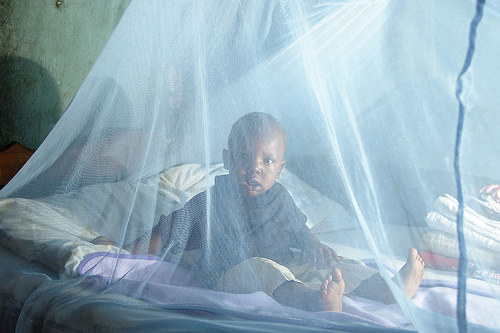 File: a child sits under a treated mosquito net: Seven employees healthcare workers Gombe in police net for diverting 5,450 Insecticides Treated Nets meant for free distributio