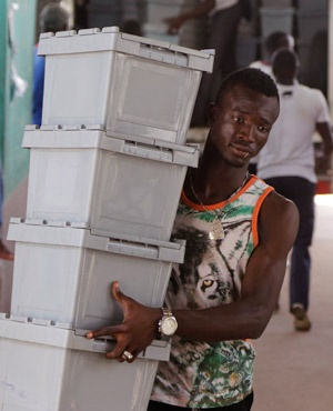 A Poll official with ballot boxes