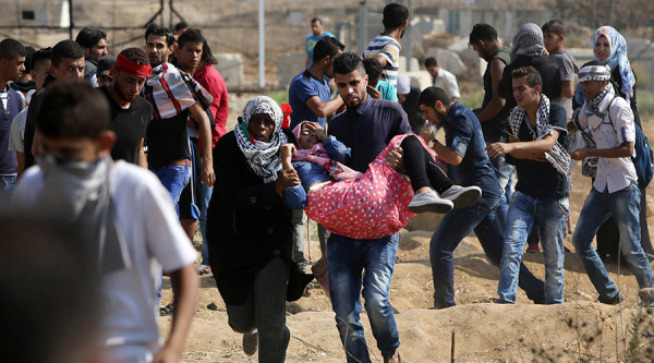 A Palestine protester being carried to safety after being injured by Israeli forces