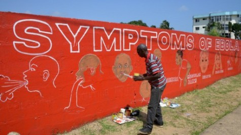 A street artist, Stephen Doe, paints an educational mural to inform people about the symptoms of the deadly Ebola virus in the Liberian capital Monrovia, on September  8, 2014.