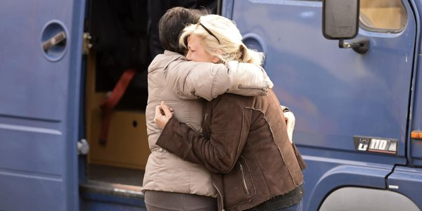 2 French women console each other at the accident scene