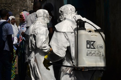 Red cross workers, wearing protective suits, get ready during a burial for victims of the virus, in Monrovia, on January 5, 2015.
