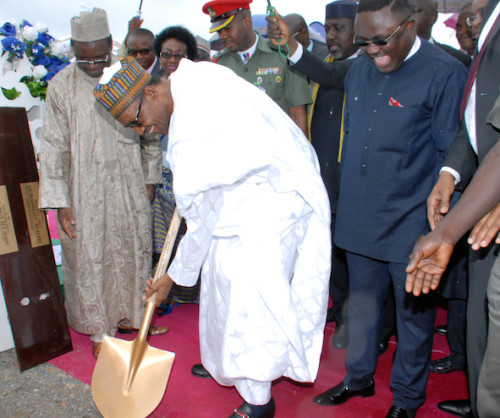 President Muhammadu Buhari performing the ground breaking duty while Governor Ben Ayade of Cross River state looks on
