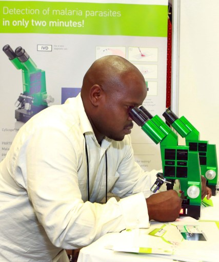 File Medical Technologist and Customer Service Director of PARTEC Alex Lope  demonstrates through a microscope the rapid detection of malaria and  diagnosis during the 6th MIM Pan-African Malaria Conference held at the International Convention Centre in Durban on October 8, 2013.The theme of the conference is - Moving Towards Malaria Elimination:Investing in Research And Control.The conference ends on October 11, 2013.AFP PHOTO /RAJESH JANTILAL