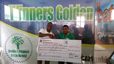 General Manager of Winners Golden Bet, Mr. Ayodele Salami (left) presents a cheque of N6,480,900 to Chigozie Ubaka Prince after winning the coupon of the company