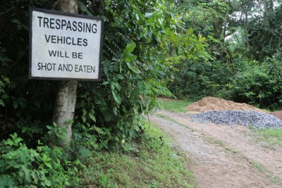 """Welcoming you to Soyinka's estate . Photo Credit Idowu Ogunleye """"On what necessitated the scary signboard, our guide,Yaya, who is one of the caretakers of the estate explained that it came about when the workers, in a bid to fend off marauders had advised Prof Soyinka to fence off the property and install a gate. However, the Nobel Laureate told his staff that he had a better idea on how to ward off potential intruders and so the scary sign board. On whether the trick had worked? Yaya replied; 'Yes. It worked like magic."""""""