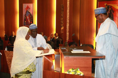 President Muhammadu Buhari watched as INEC National Commissioner, Hajia Amina Zakari signs the oath book during the swear-in ceremony