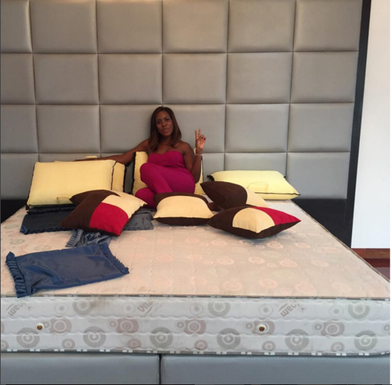 Linda poses on her bare bed in Banana island