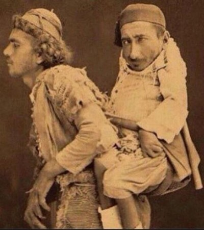 The one being carried is a Christian dwarf named Sameer. The one carrying him is a blind Muslim named Mohammed