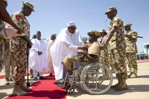 Buhari decorates Kenneth Kulugh with the Purple Heart medal for gallantry