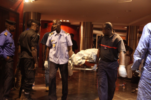 Mali security personal carry the body of a victim inside the Radisson Blu hotel after the attack by terrorists