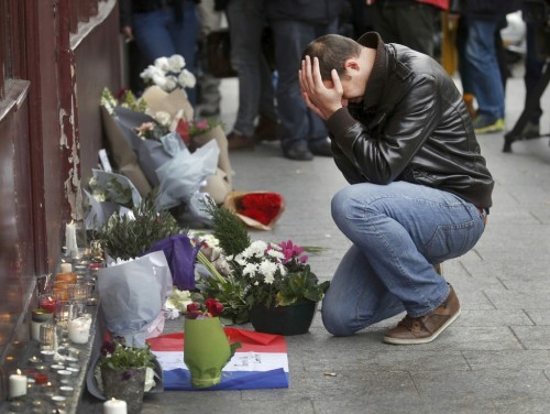 Paris attacks: a mourner pays tribute at a site of the attacks