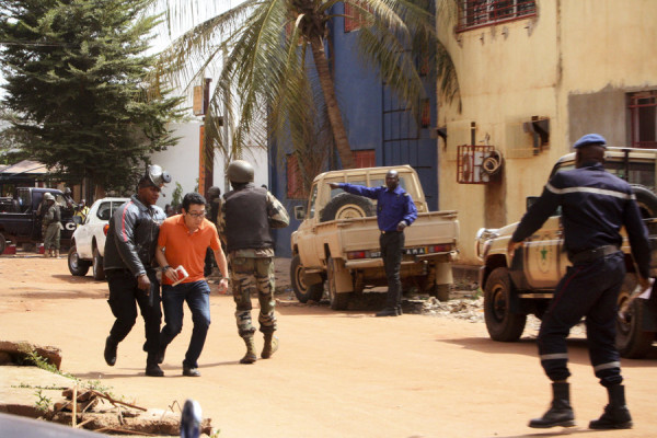 A foreigner being taken away from the besieged hotel by Malian forces