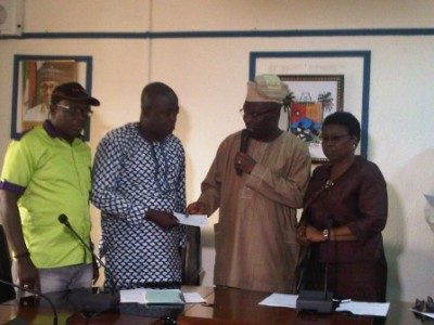 Commissioner for Special Duties and Inter-Governmental Relations, Mr Seye Oladejo, presenting, right, the N5 million cheque to Mr. Okeoseye Odiah