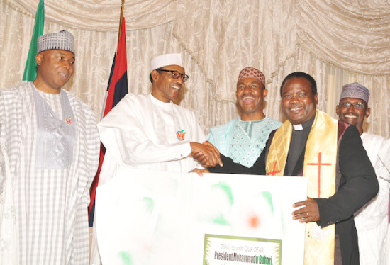 Chairman of the Christian Association of Nigeria (CAN) Abuja Chapter , Pastor Israel Akanji, presenting a Christmas Card on behalf of the Christian community to President Muhammadu Buhari when FCT residents paid a  Christmas Homage   on the President at the Presidential Villa . Others are Senate President Bukola Saraki,  Executive Secretary of Nigerian Pilgrims Commission Mr. Kennedy Opara, and FCT Minister Mohammed Bello.