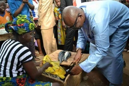 Governor Fayose cutting fish in the market