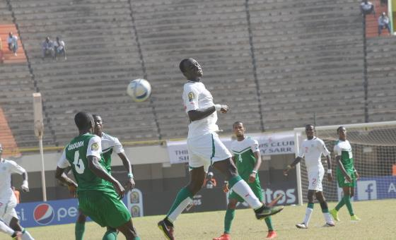 A senegalese player leaps for the ball as Nigerians wait in anticipation