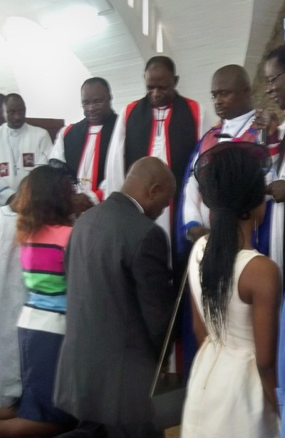 Professor Abel Idowu Olayinka in  black suit and his family as the officiating minister prays for them