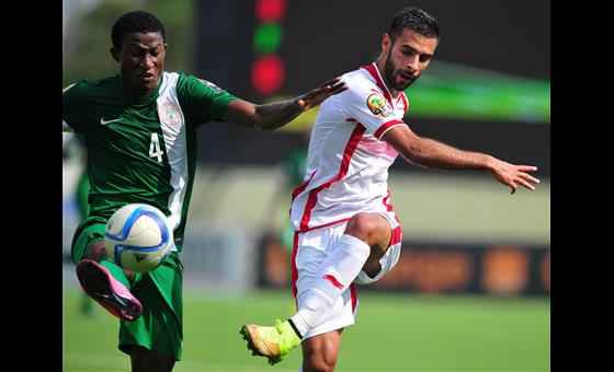 A Nigerian player battles for the control of the ball against Tunisian opponent