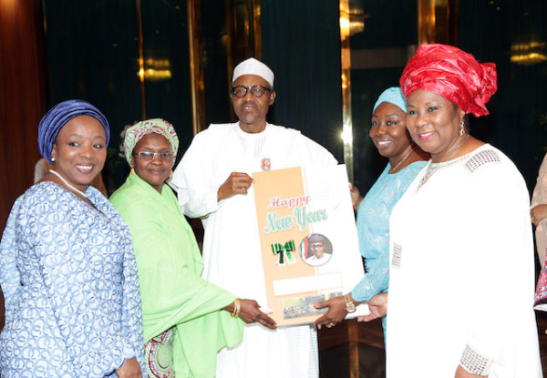 Buhari receives a New Year card from the women. Photo Sunday Aghaeze