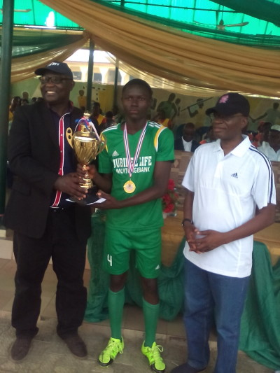Captain of Redeemer'sHigh School, Mowe (middle) receives   football trophy from Pastor Akin John of RCCG (left)
