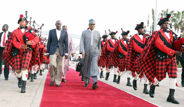 President Buhari accompanied by the NSA Major General Babagana Monguno walks through the guard of honour formed by the 'presidential flutists'