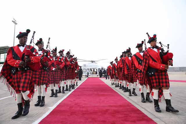 The bagpipers line the route to the Presidential chopper, in the background