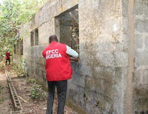 An EFCC official examines the house before the handover