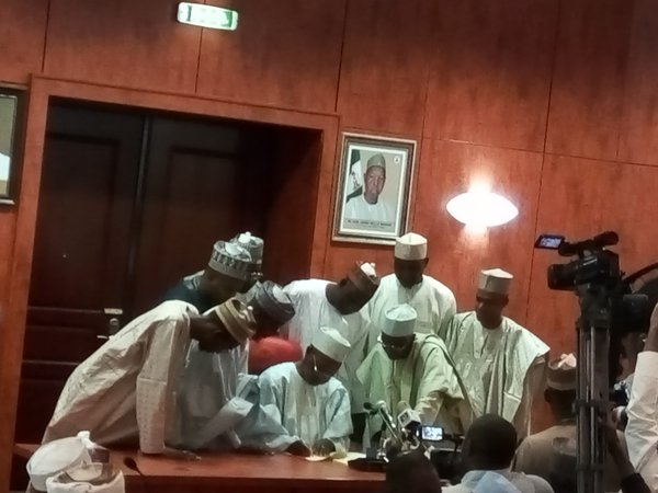 Masari signs the budget, surrounded by aides