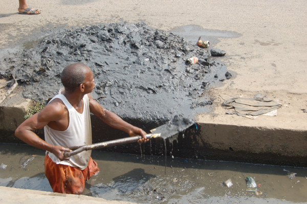 A worker clears the drains in Lagos