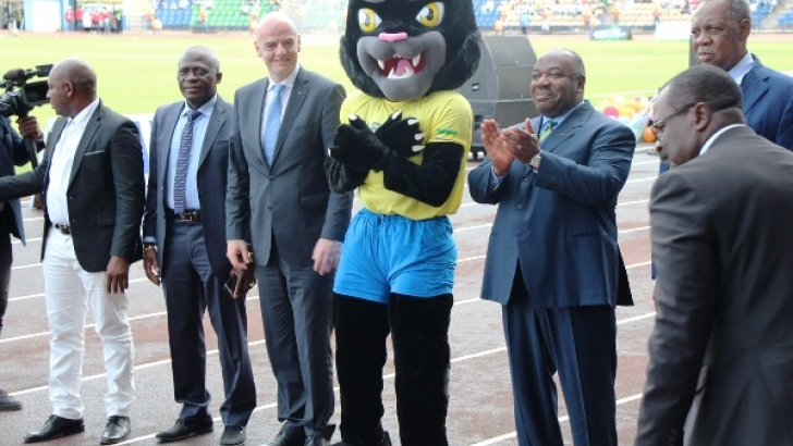 The Mascot with Gabonese President, right and FIFA President, Infantino, left. CAF President Hayatou, stands behind Gabon's leader