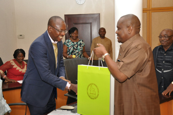 Wike hands over a gift to a media correspondent