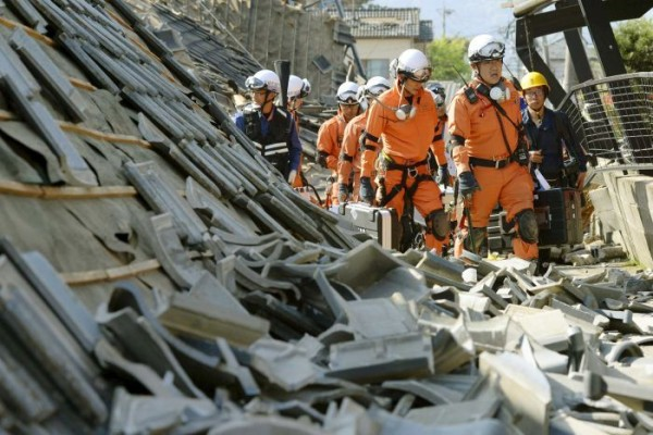 Rescue workers rifle through fallen houses looking for trapped people