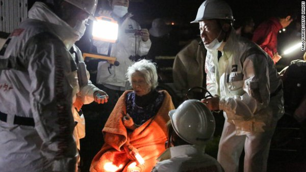 An elderly woman receives attention from rescue workers