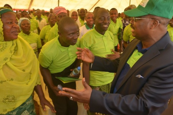 Governor Abiola Ajimobi chats  with beneficiaries of the state's  agriculture initiative during the launch of the programme, in Paago,  Iseyin