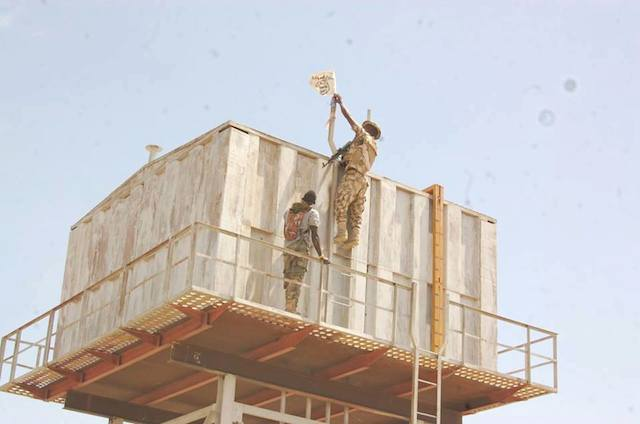 a Soldier removes a Boko Haram flag on a water tank