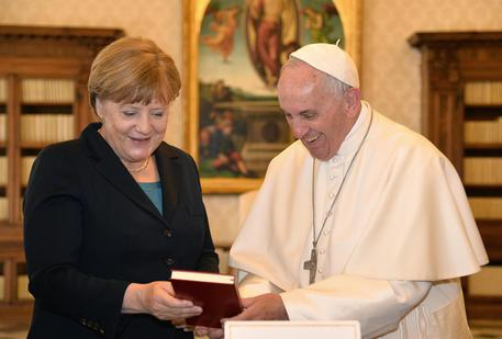 German Chancellor Angela Merkel (L) exchanges gifts with Pope Francis during a private audience on May 6, 2016 at the Vatican. Merkel is in Rome to take part in a ceremony for the awarding of Germany's famed Charlemagne Prize to Pope Francis, given to public figures in recognition of contribution to European unity. ANSA/ ALBERTO PIZZOLI/AFP/POOL