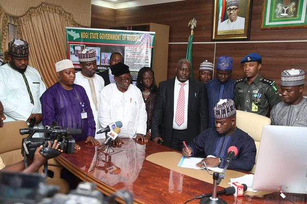 Governor Bello:  signs amidst witnesses.