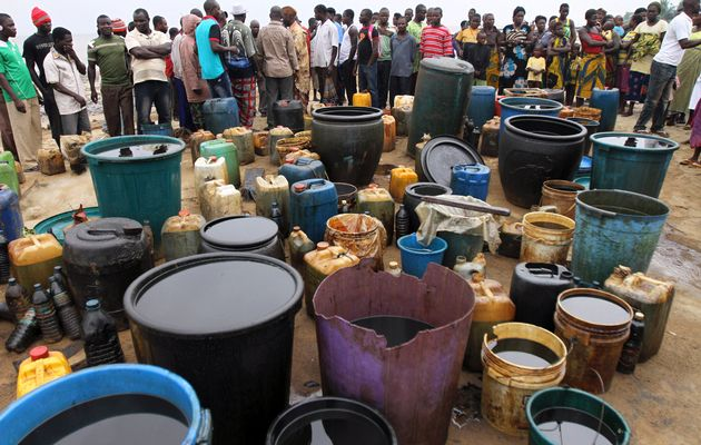 Villagers stand next to crude oil collected in containers at the shore of the Atlantic ocean near Orobiri village, days after a Royal Dutch Shell's Bonga off-shore oil spill, in Nigeria's delta state