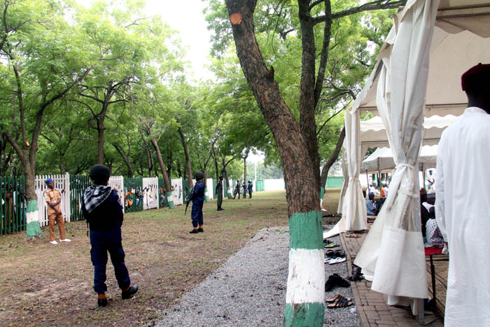 Well armed security operatives keep watch to ensure there is no straying from the commoners' ground where trees are providing shade for the worshipers to the privileged area where the VIPs and their family members are praying under tents