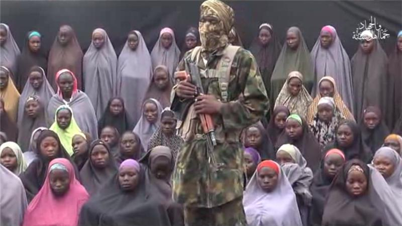 Grab from the new video by Boko Haram shows the fighter and the girls surrounding him. Credit-Al-jazera