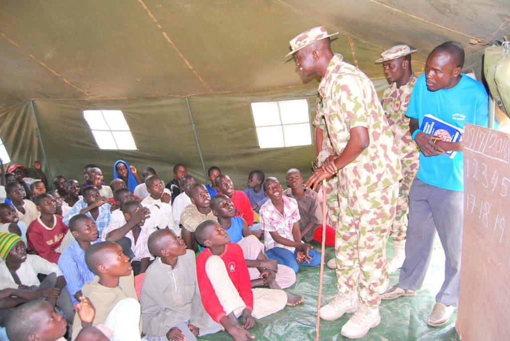 A Soldier attending to pupils in the 'classroom'