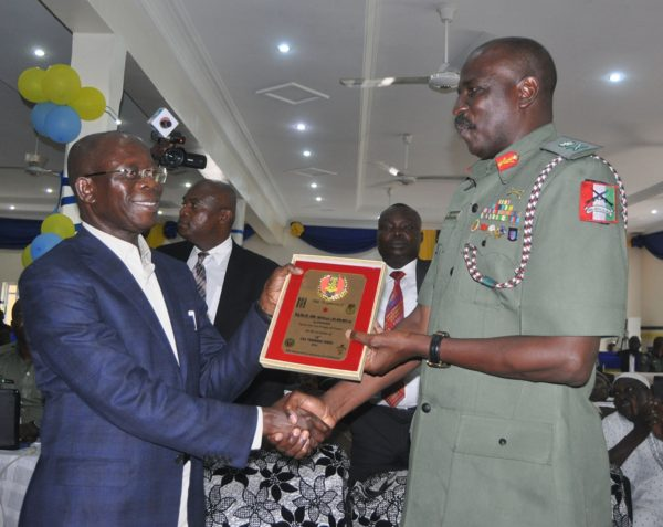 Maj-Gen Ahmed Mohammed, Corps Commander Infantry, Nigerian Army, representing the Chief of Army Staff, Lt-Gen Tukur Buratai (right) presents a souvenir to Governor Adams Oshiomhole at the Nigerian Army's 18th Combat Service Support Training Week held at the Nigerian Army School of Supply and Transport, Benin City, on Tuesday.