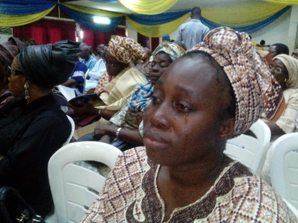 A woman shedding tears at the service